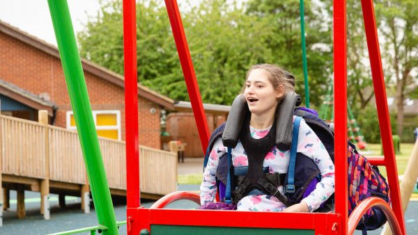 Girl using wheelchair swing at Swings & Smiles