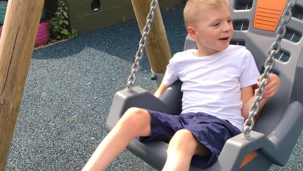 Boy playing on swings at Swings & Smiles